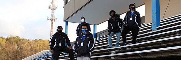 TV crew poses in stands