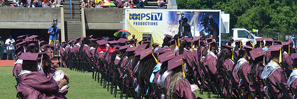 rows of graduates with TV truck in background