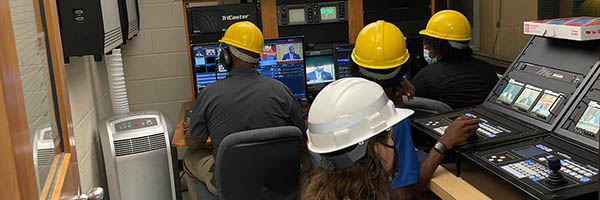 4 people with hardhats in TV studio under construction